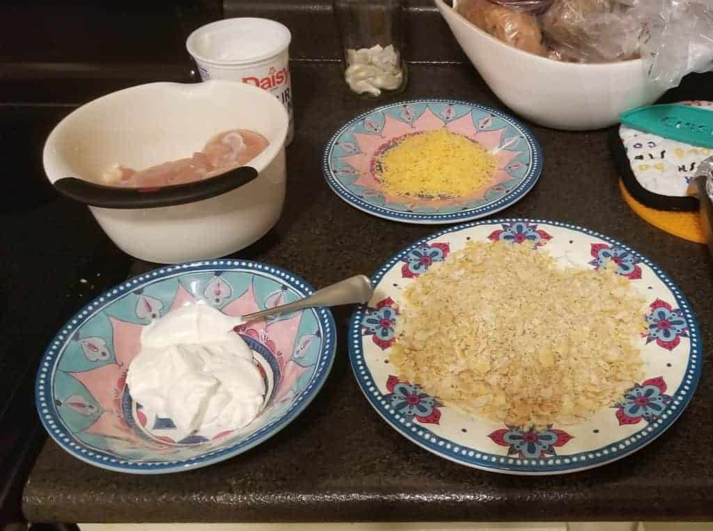 Bowls of chicken and sour cream and plates of cracker crumbs and cheese on a kitchen counter.
